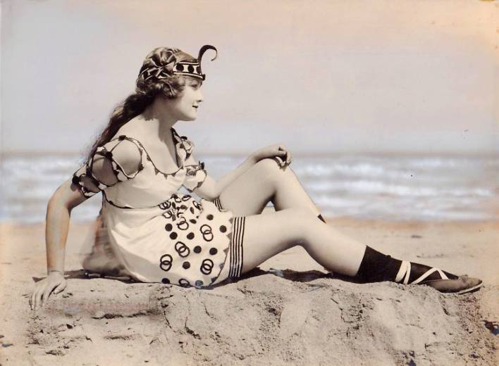 photo-chicago-exhibit-supply-company-photo-for-arcade-card-woman-sitting-profile-on-beach-with-elaborate-bathing-suit-tinted-1920s